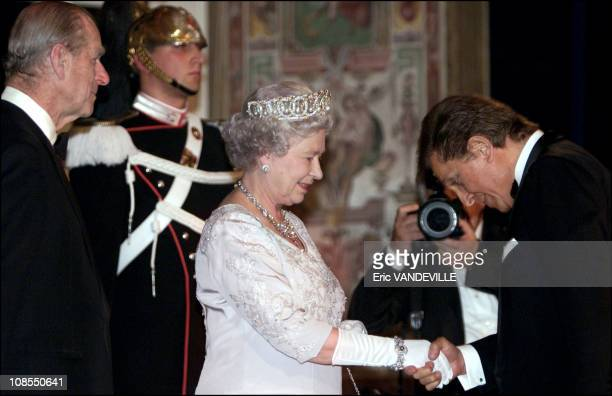 Britain's Queen Elizabeth together with Prince Philip shakes hands with fashion designer Valentino at Quirinal presidential palace before the state...