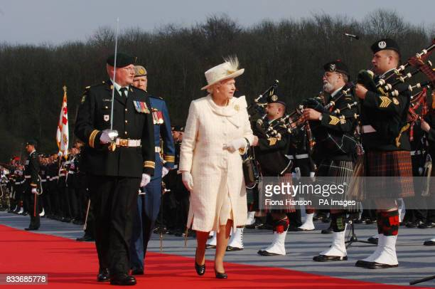 Britain's Queen Elizabeth walks past a line of pipers as she inspects a Canadian guard of honour during a ceremony at the Vimy memorial near Lille in...