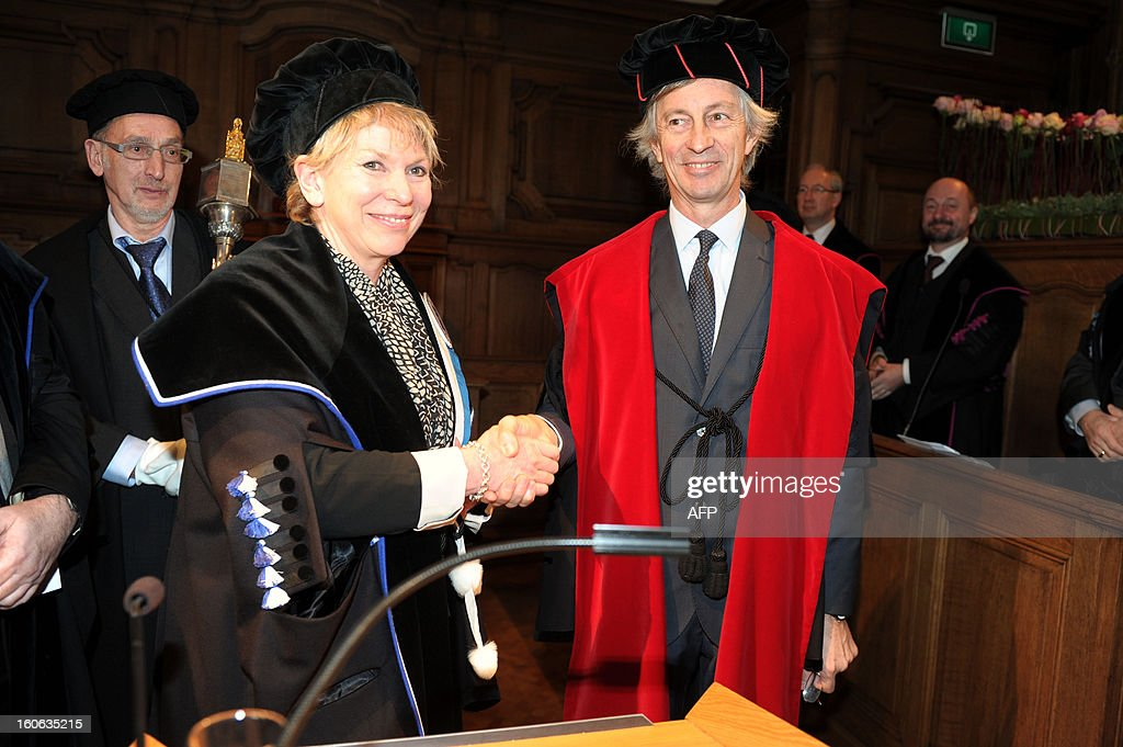 Britain's science writer, lecturer and broadcaster who specialises in the human brain Rita Carter (L) shakes hands with KUL's Rector Mark Waer during a press conference ahead of the honorary degrees ceremony on the occasion of the KU Leuven university's Patron Saint's Day, on February 4, 2013.