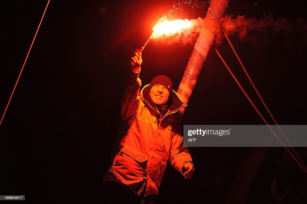 Britain's skipper Mike Golding holds a torch as he celebrates on his monohull 'Gamesa' as he finished sixth of the 7th edition of the Vendee Globe solo round-the-world race on February 6, 2013 in Les Sables-d'Olonne, western France.