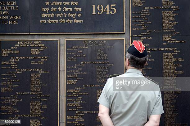Britain's top military chief General David Richards watches a memorial plaque during a visit to the war cemetery in Yangon on June 4 2013 Richards is...
