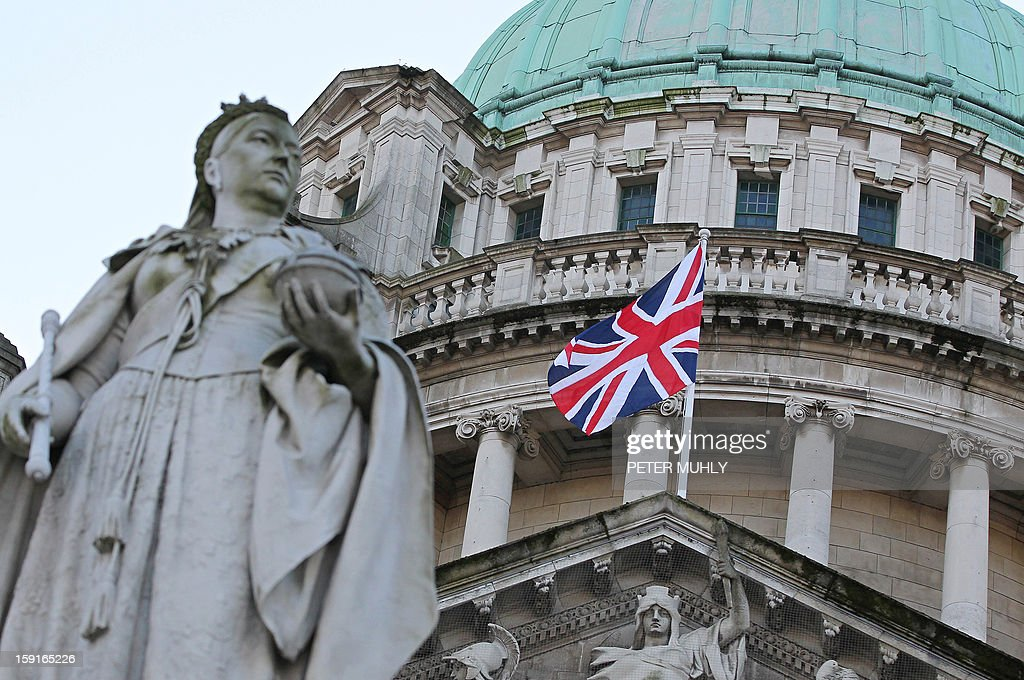Britain's Union flag flies behind a statue of Queen Victoria at the Belfast City Hall in Belfast, Northern Ireland, on January 9, 2013. The British flag was hoisted over Belfast's City Hall on Wednesday for the first time since its removal a month ago sparked riots in Northern Ireland. The emblem will now fly for a maximum of 18 days a year including British royal birthdays -- the first of which fell on Wednesday as Prince William's wife Catherine turned 31. AFP PHOTO / PETER MUHLY