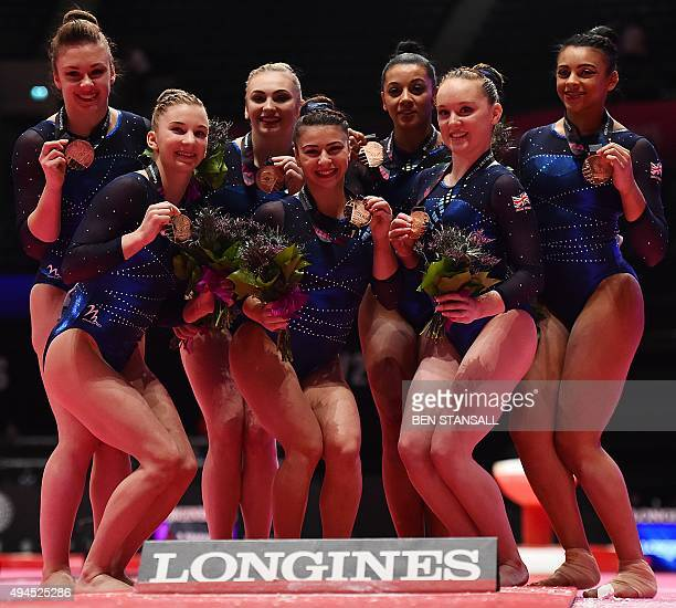 Britain's women's team celebrate with their bronze medals following the Women's Team event final on the fifth day of the 2015 World Gymnastics...