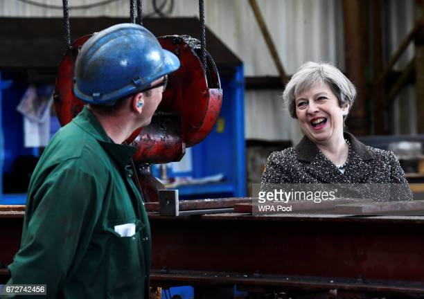 Britain'sPrime Minister Theresa May chats to a worker as she visits a steel works on April 25 in Newport Wales Theresa May visits Wales on the back...