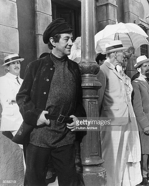 British actor Alec Guinness dressed as a Bolshevik watching a World War I recruitment parade with amusement in a still from director David Lean's...