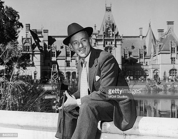 British actor Alec Guinness holds a Rolleiflex camera while seated near a pond in front of the Biltmore House during the shooting of the film 'The...
