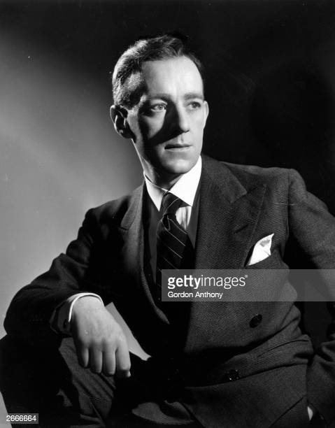 British actor Alec Guinness wearing a suit