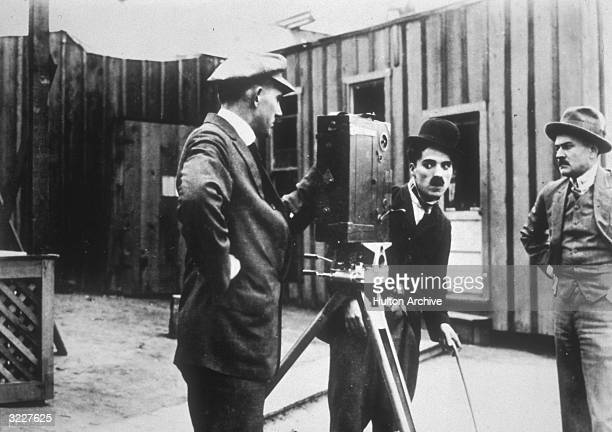 British actor and director Charles Chaplin in costume as the Tramp looks into a movie camera as two cameramen stand by in a still from director Henry...