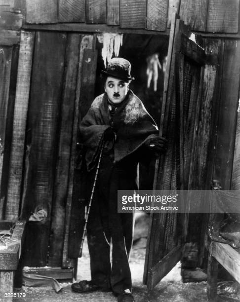 British actor and director Charles Chaplin looks through an open door in the snow in a fulllength still from his film 'Gold Rush'