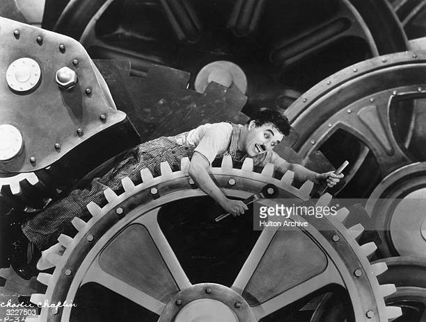 British actor and director Charles Chaplin wearing overalls and holding a wrench sits on an enormous set of gears in a still from Chaplin's film...