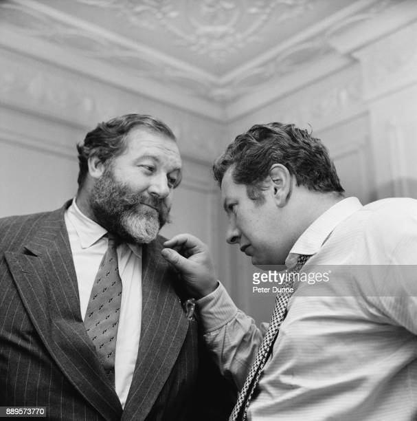British actor and filmaker Peter Ustinov after getting a beard cut by a barber checks the beard of character actor James Robertson Justice UK 24th...