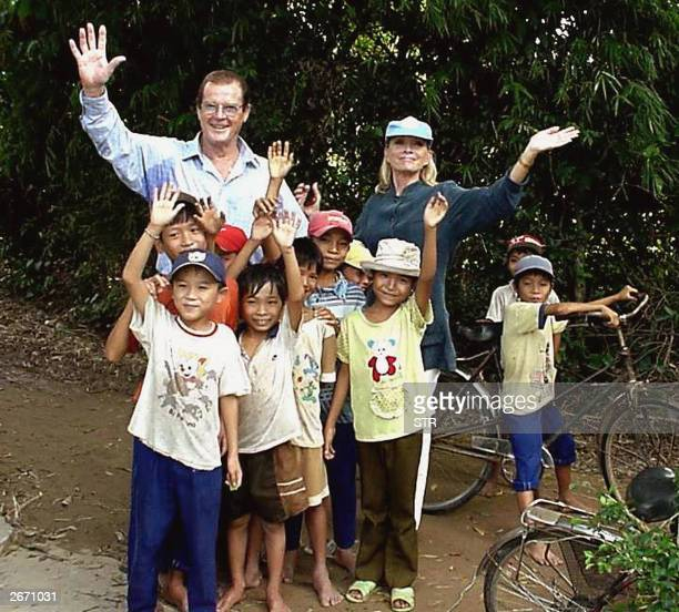 British actor and former James Bond star Sir Roger Moore and his wife Kristina wave as they pose with children during a visit made 28 October 2003 in...