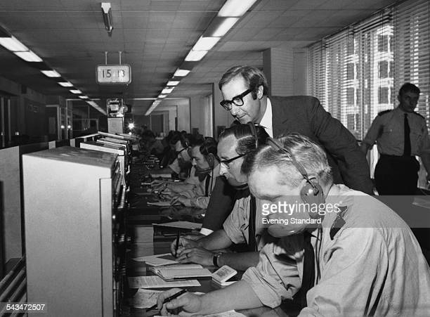 British actor and television presenter Shaw Taylor at the police switchboard in the Information Room during a visit to Scotland Yard London circa...