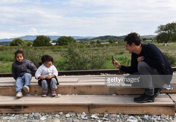 British actor and UNICEF Goodwill Ambassador Orlando Bloom takes pictures of two refugees girls during his visit at the refugee registration camp...