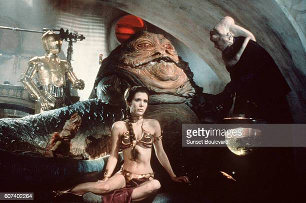 British actor Anthony Daniels American Carrie Fisher and Scottish Michael Carter on the set of Star Wars Episode VI Return of the Jedi directed by...