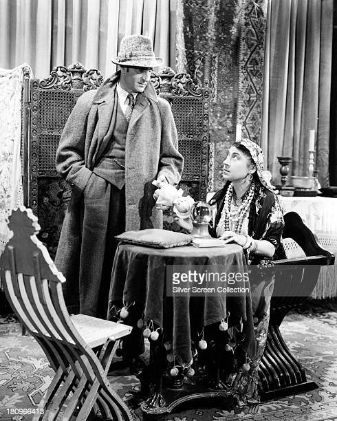 British actor Basil Rathbone as Sherlock Holmes visiting a fortune teller in 'Pursuit To Algiers' directed by Roy William Neill 1945
