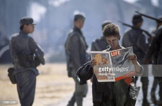 British actor Christian Bale as Jim Graham reading a copy of Life magazine in a scene from the film 'Empire of the Sun' 1987