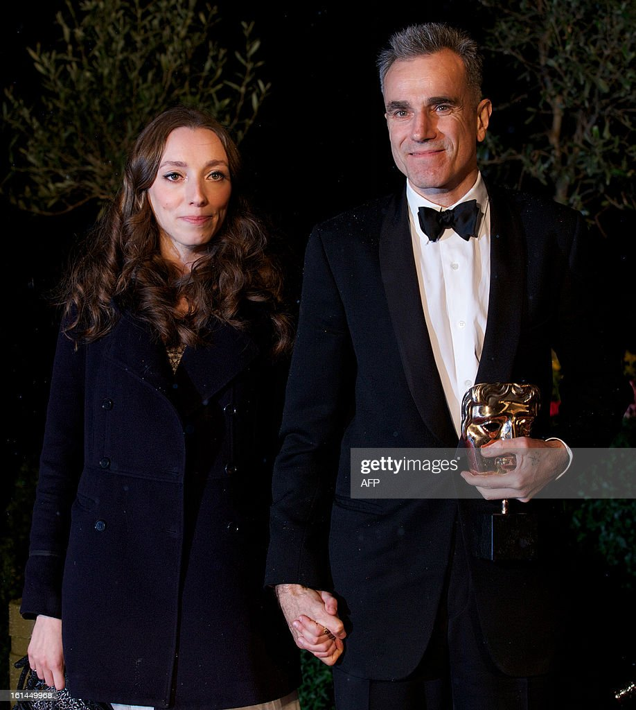 British actor Daniel Day-Lewis holds his leading actor award as he poses with Charissa Shearer arriving for the BAFTA British Academy Film Awards after party in London on February 10, 2013.