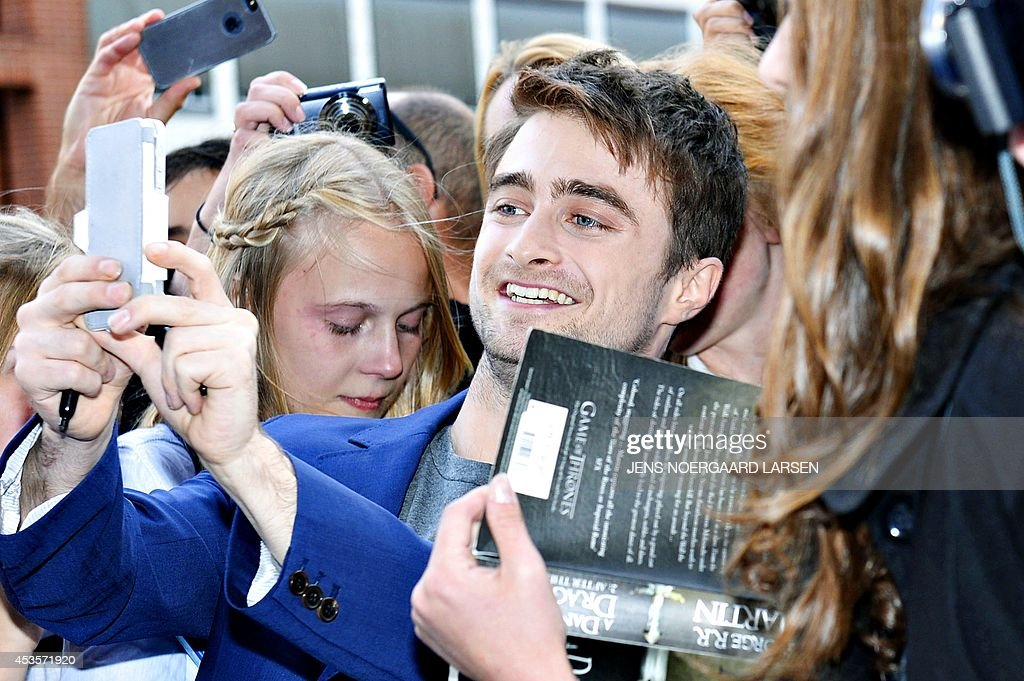British actor Daniel Radcliffe (C) takes a picture with fans in front of the Imperial Cinema in Copenhagen on August 13, 2014 prior to the gala premiere of his last movie 'What If' directed by Canadian Director Michael Dowse. AFP PHOTO / SCANPIX DENMARK / JENS NOERGAARD LARSEN ** Denmark out **