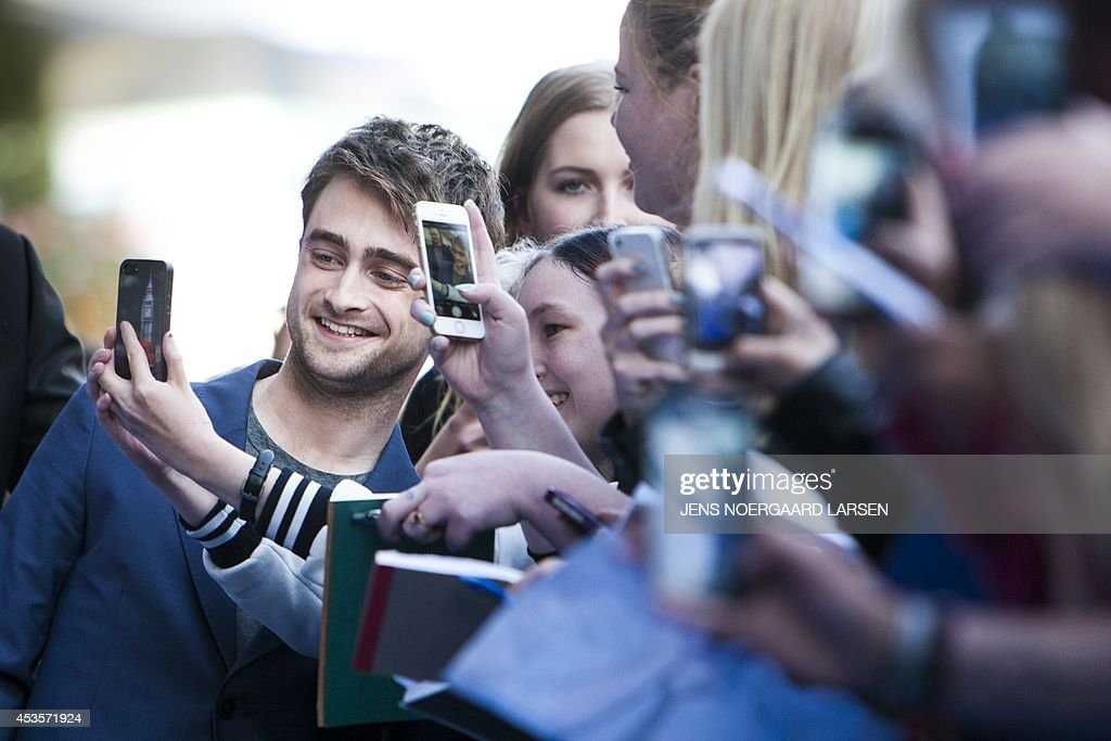 British actor Daniel Radcliffe (L) takes a picture with fans in front of the Imperial Cinema in Copenhagen on August 13, 2014 prior to the gala premiere of his last movie 'What If' directed by Canadian Director Michael Dowse. AFP PHOTO / SCANPIX DENMARK / JENS NOERGAARD LARSEN ** Denmark out **