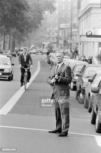 British actor Edward Woodward who plays exagent Robert McCall in the American television series The Equalizer posing in London with a submachine gun...