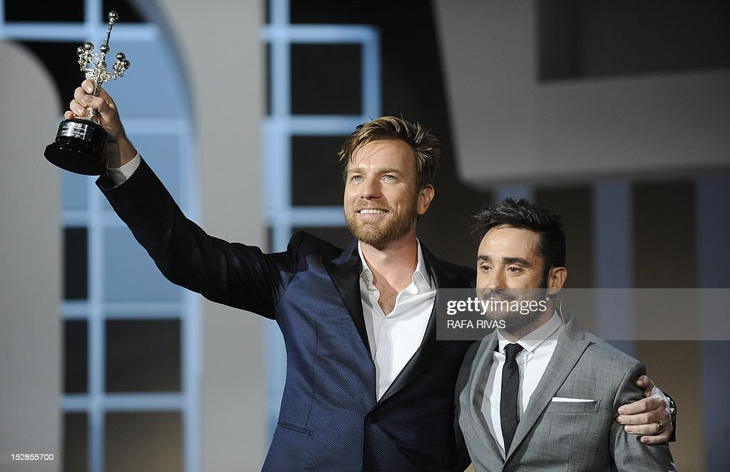 British actor Ewan McGregor (L) raises his award as he receives the 60th San Sebastian International Film Festival's 'Donostia' award from Spanish director Juan Antonio Bayona (R), on September 27, 2012, in the northern Spanish Basque city of San Sebastian. AFP PHOTO/ RAFA RIVAS