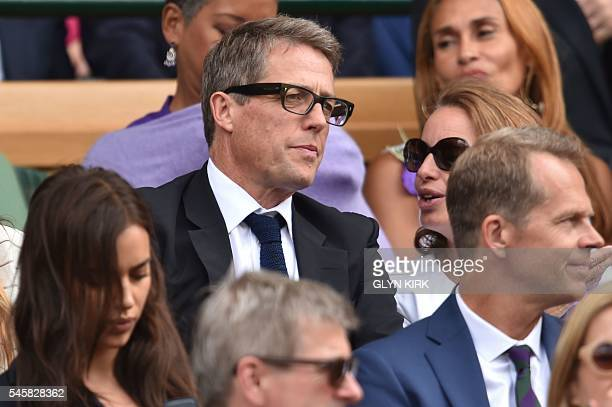 British actor Hugh Grant sits in the royal box on centre court before the start of the men's singles final match on the last day of the 2016...