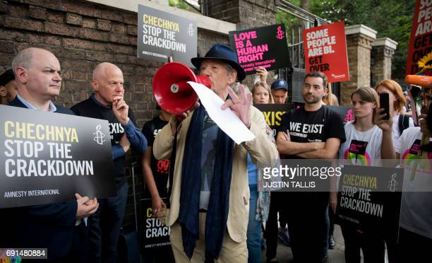 British actor Ian McKellen speaks through a megaphone during a protest over an alleged crackdown on gay men in Chechnya outside the Russian Embassy...