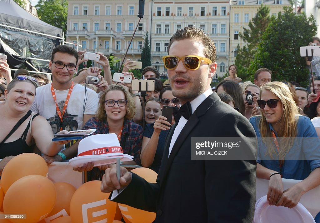 British actor Jamie Dornan greets his fans on the red carpet upon arrival for the opening ceremony of the 51th Karlovy Vary International Film Festival (KVIFF) in Karlovy Vary, Czech Republic on July 1, 2016. / AFP / Michal Cizek