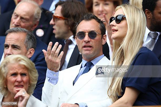British actor Jude Law and partner Philippa Coan sit in the royal box on centre court before the men's semifinal match on the twelfth day of the 2016...