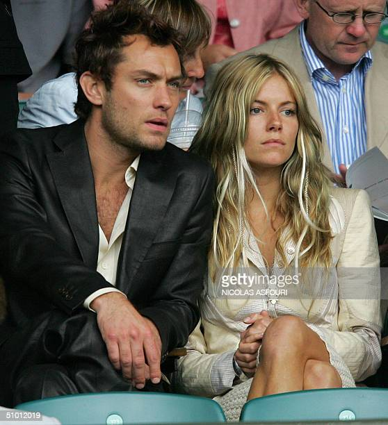 British actor Jude Law and Sienna Miller take their seats to watch Roger Federer of Switzerland play Lleyton Hewitt of Australia before their...