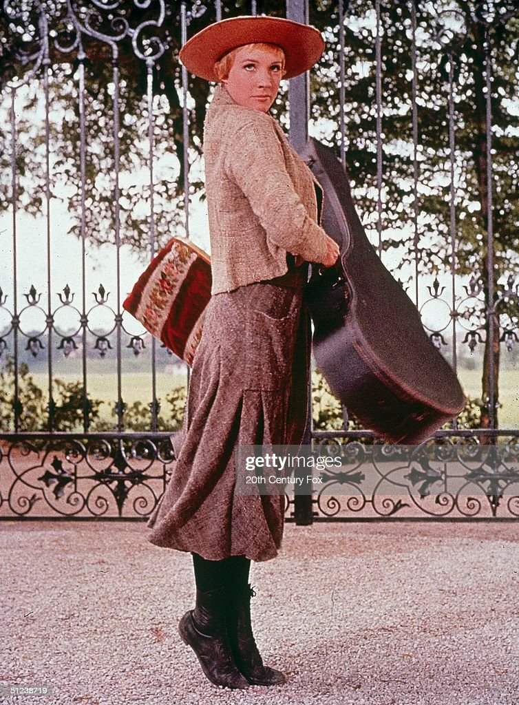 1965, British actor Julie Andrews holds a guitar case and a carpet bag in a still from the film 'The Sound of Music' directed by Robert Wise.