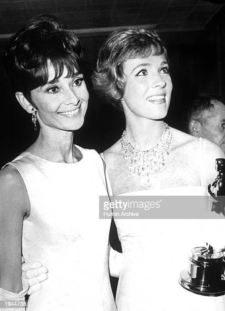 British actor Julie Andrews holds her Oscar while standing with Belgian born actor Audrey Hepburn at the Academy Awards ceremonies in Santa Monica...