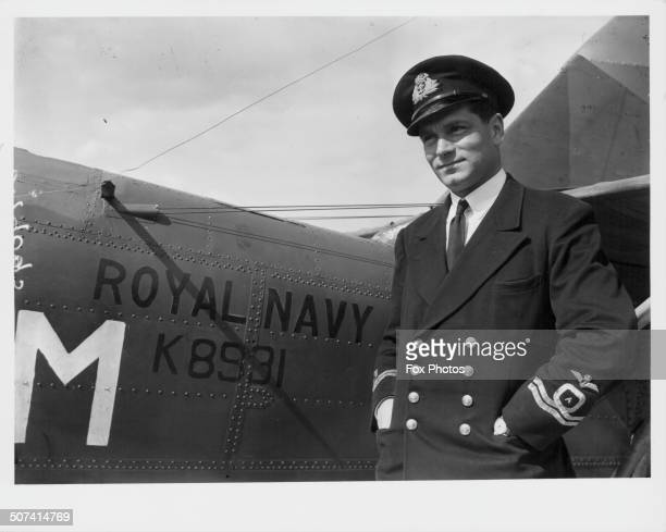 British actor Laurence Olivier in his pilot uniform standing next to a Royal Navy aircraft in service at a Fleet Air Arm Station during World War Two...