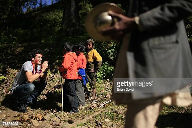 British actor Orlando Bloom wearing flower garlands and a red 'tikka' mark on his forehead greets boys with the traditional South Asian gesture of...