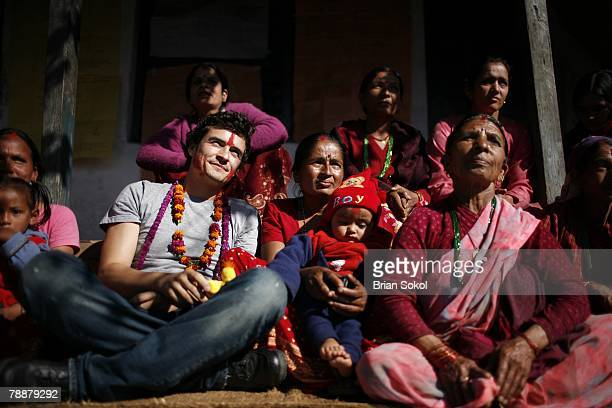 British actor Orlando Bloom wearing flower garlands and a red 'tikka' mark on his forehead sits with children and women members of the Kaule...
