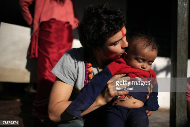 British actor Orlando Bloom wearing flower garlands and a red 'tikka' mark on his forehead kisses a sleeping baby in the village of Kalika on January...