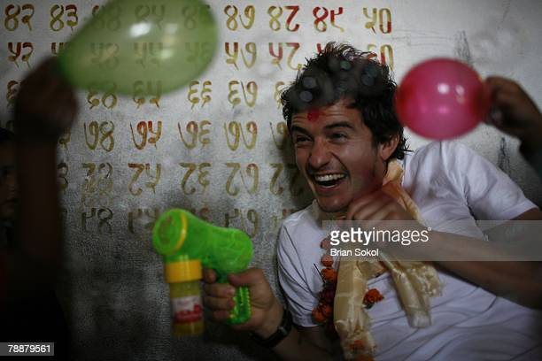 British actor Orlando Bloom wearing flower garlands and a red 'tikka' mark on his forehead playfully points a bubbleblower toy at first graders...