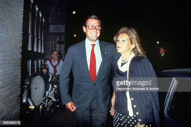 British actor Roger Moore and his Italian wife Luisa Mattioli walking in a street of Rome 1988