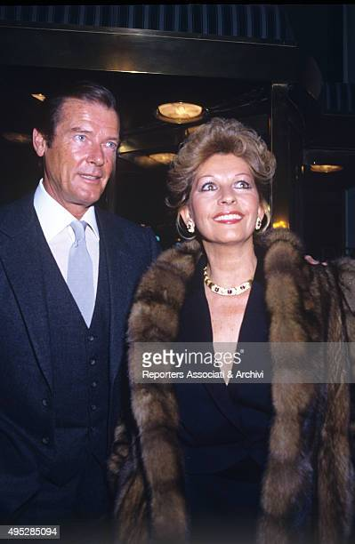 British actor Roger Moore and his wife Luisa Mattioli attending a fashion show at the Excelsior Hotel Rome 1982