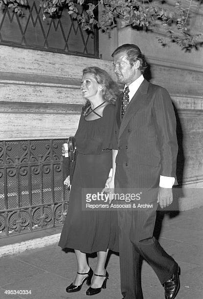 British actor Roger Moore and his wife Luisa Mattioli walking in the streets of Rome by night Rome June 1975