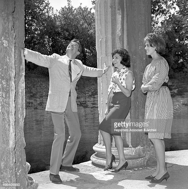British actor Roger Moore Italian actress Luisa Mattioli and Italian actress and singer Giorgia Moll visiting the Roman Forum in a break on the set...