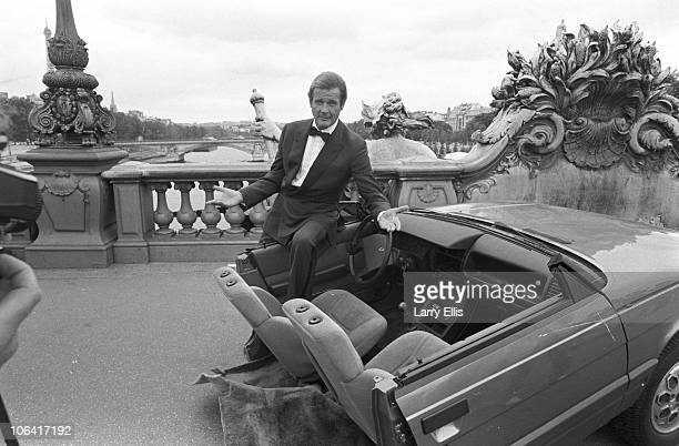 British actor Roger Moore on set of the James Bond movie 'A View to a Kill' with half a car during filming in Paris France in August 1984
