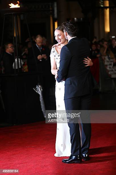 British actor Sam Claflin greets his pregnant wife British actress Laura Haddock as she arrives on the red carpet attend the UK Premiere of the film...