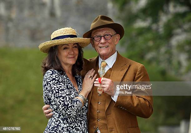 British actor Sir John Hurt poses with his wife Anwen after being awarded a knighthood by Queen Elizabeth II during an Investiture ceremony at...