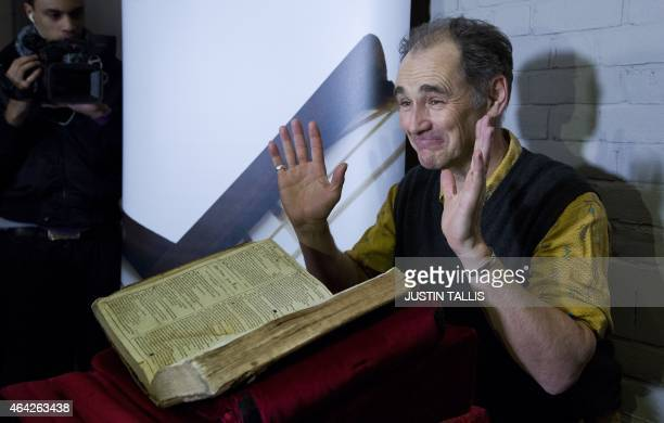 British actor theatre director and playwright Mark Rylance poses for pictures with the recently discovered SaintOmer First Folio during a photocall...