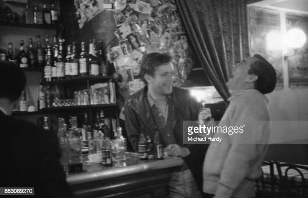 British actor Tony Hancock laughing with Canadian actor Paul Massie at a bar 12th September 1960