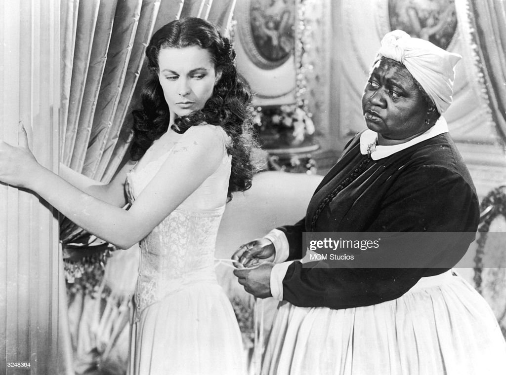 British actor Vivien Leigh holds on to a pillar as American actor Hattie McDaniel tightens her corset in a still from the film 'Gone with the Wind'...