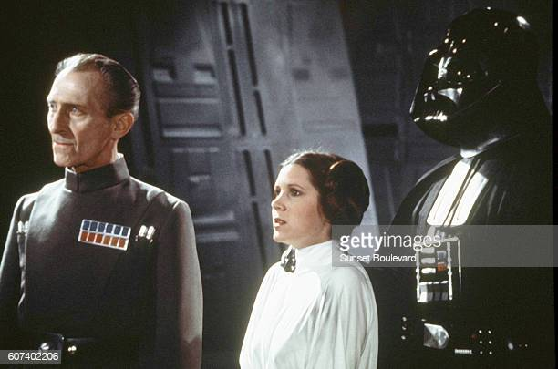 British actors Peter Cushing David Prowse and American actress Carrie Fisher on the set of Star Wars Episode IV A New Hope written directed and...