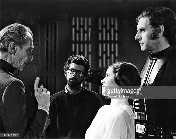 British actors Peter Cushing David Prowse and American Actress Carrie Fisher with director screenwriter and producer George Lucas on the set of his...